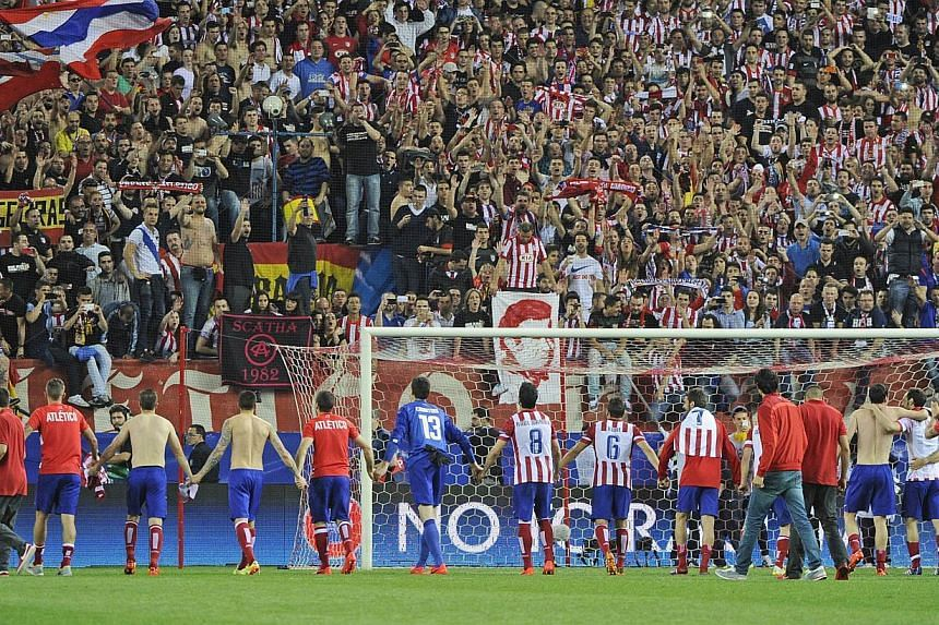Atletico Madrid players celebrate winning 1-0 after the UEFA Champions League quarter final football match Club Atletico de Madrid vs Barcelona at the Vicente Calderon stadium in Madrid on April 9, 2014. -- PHOTO: AFP