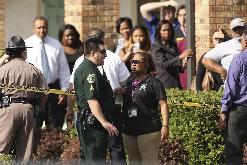 Parents wait behind a police line after a child was killed and a dozen children injured when a car slammed into a daycare centre in Florida on Wednesday after being struck by a hit-and-run driver. -- PHOTO: REUTERS