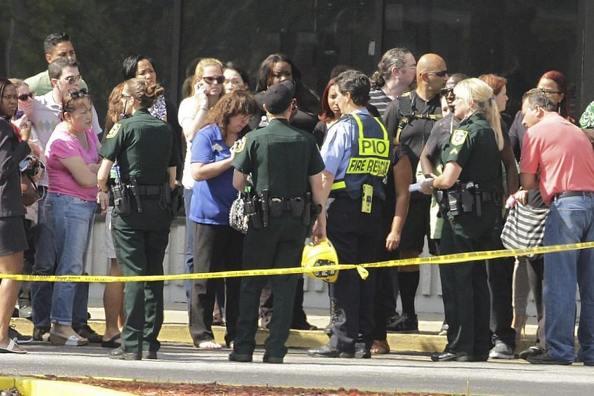 Parents and onlookers speak to police officers after a vehicle crashed into the KinderCare Learning Center in Winter Park, Florida on April 9, 2014. -- PHOTO: REUTERS