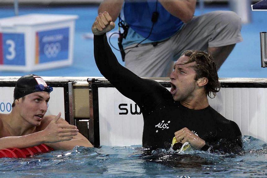 Australia's Ian Thorpe punches the air after winning the 200m freestyle in an Olympic record time of 1min 44.71sec, as second-placed Pieter van den Hoogenband of Holland leans across to congratulate him. -- ST FILE PHOTO: ALBERT SIM