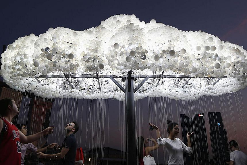 """People pose for pictures with Wayne Garrett and Caitlind Brown of Canada's light installation """"CLOUD"""" during a media preview of the i Light Marina Bay festival in Singapore March 6, 2014. -- FILE PHOTO: REUTERS"""