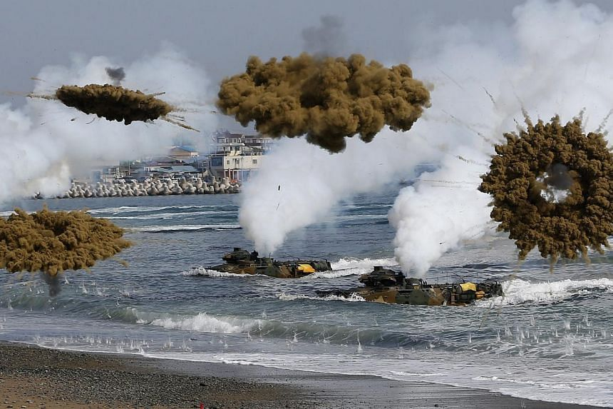 Amphibious assault vehicles of the South Korean Marine Corps throwing smoke bombs as they move to land on shore during a US-South Korea joint landing operation drill in Pohang March 31, 2014. The drill is part of the two countries' annual military tr