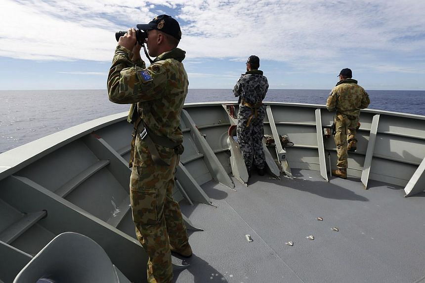 Gunner Richard Brown (left) of Transit Security Element on the lookout on the forecastle of HMAS Perth in the search for missing Malaysia Airlines flight MH370 in the southern Indian Ocean on April 7, 2014. -- FILE PHOTO: AFP/AUSTRALIAN DEFENCE