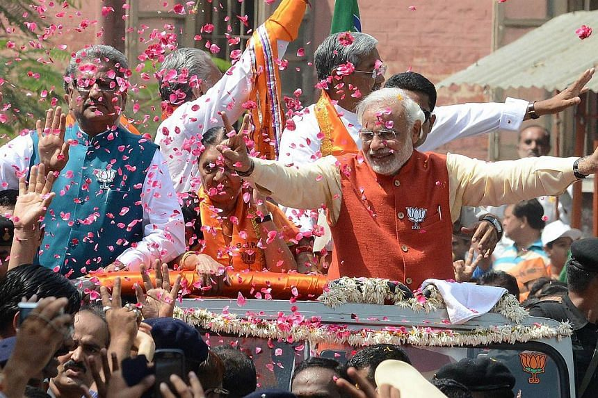 Bhartiya Janta Party Prime Ministerial candidate Narendra Modi (centre) is showered with flower petals during his roadshow in Vadodara, Gujarat. Mr Modi has acknowledged for the first time that he is married, solving one of the biggest mysteries abou