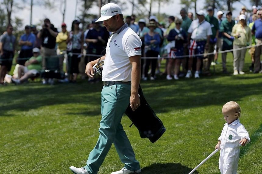 US golfer Ryan Moore and his son Tucker (right) walk along the third hole during the Par 3 contest ahead of the Masters golf tournament at the Augusta National Golf Club in Augusta, Georgia on April 9, 2014.Moore won the event that no one wants