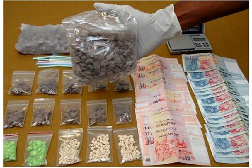 Part of the drugs and cash seized in an operation conducted in Simei by Home Team officers on April 9, 2014. -- PHOTO: CENTRAL NARCOTICS BUREAU