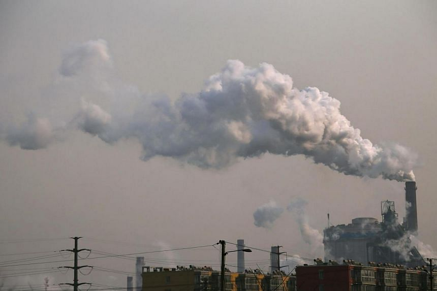 Smoke rises from a chimney of a steel plant next to residential buildings on a hazy day in Fengnan district of Tangshan, Hebei province on Feb 18, 2014.Nearly 2,000 Chinese enterprises were found to be in violation of state pollution guidelines