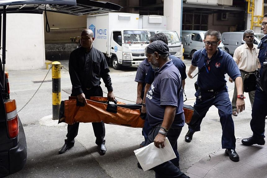 The body of the tourist who was found dead in a room at the Peninsula Excelsior Hotel being taken away on April 10, 2014. -- ST PHOTO: DESMOND LIM