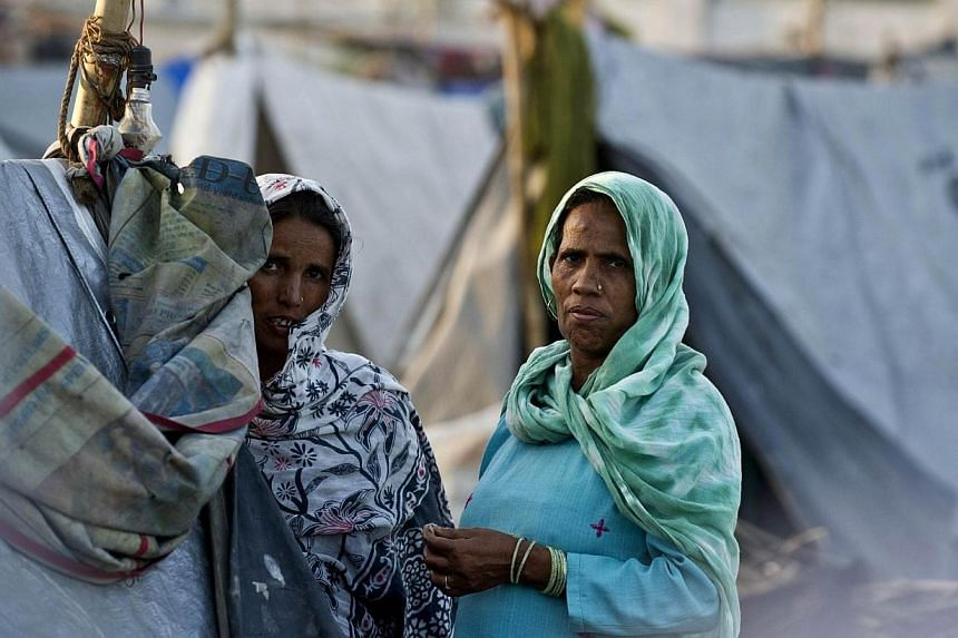 In this photograph taken on April 9, 2014, Indian residents displaced by riots, look on as others speak outside their temporary shelters in the village of Jaula in Muzaffarnagar District, before returning to their native villages to vote in national