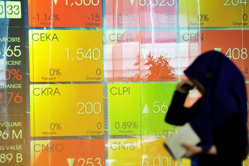 A woman walks past the Jakarta Stock Exchange display panel in Jakarta on April 10, 2014. An unexpectedly weak election result for the party behind the frontrunner to be Indonesia's next president hurt stocks and the currency on Thursday.-- PHO