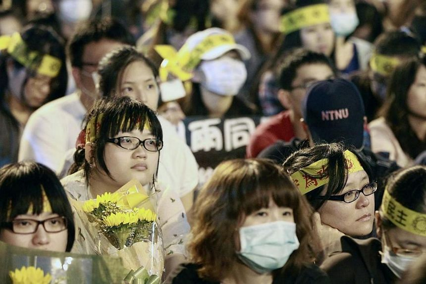 Activists holding sunflowers take part in a gathering outside as protesters, whom they support, leave Taiwan's parliament in Taipei on Thursday, April 10, 2014.Student activists on Thursday ended an unprecedented three-week occupation of Taiwan