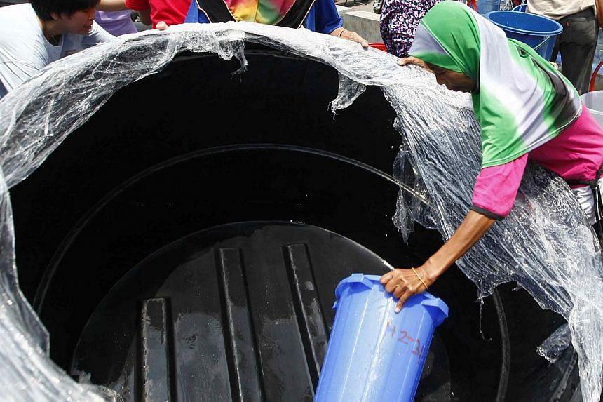 Residents scoop water at Taman Setia Balokong, outside Kuala Lumpur on Feb 25, 2014. -- FILE PHOTO: REUTERS