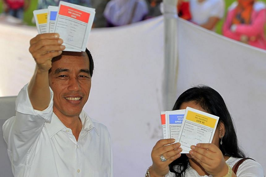 Jakarta governor and presidential candidate from the Indonesian Democratic Party-Struggle (PDI-P) party, Joko Widodo, and his wife Iriana show their ballot papers during voting in the parliamentary elections in Jakarta April 9, 2014. -- PHOTO: REUTER