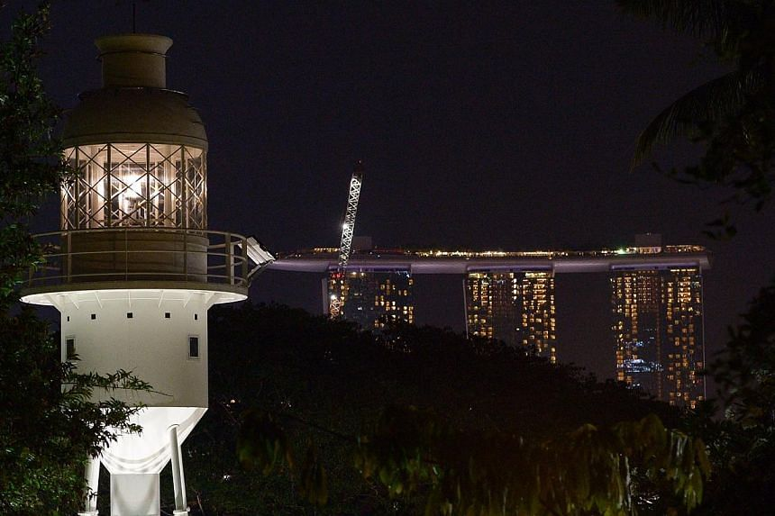 Fort Canning Park's lighthouse shone out for the first time in more than half a century on Friday night for the launch of Singapore's first maritime trails. -- ST PHOTO:DESMOND WEE TY