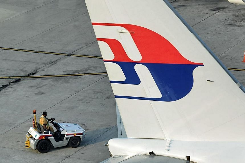 A ground staff member drives a tow vehicle past a Malaysia Airlines plane parked at the terminal in Kuala Lumpur Intenational Airport in Sepang on March 30, 2014.Malaysia's government has begun investigating civil aviation and military authorit