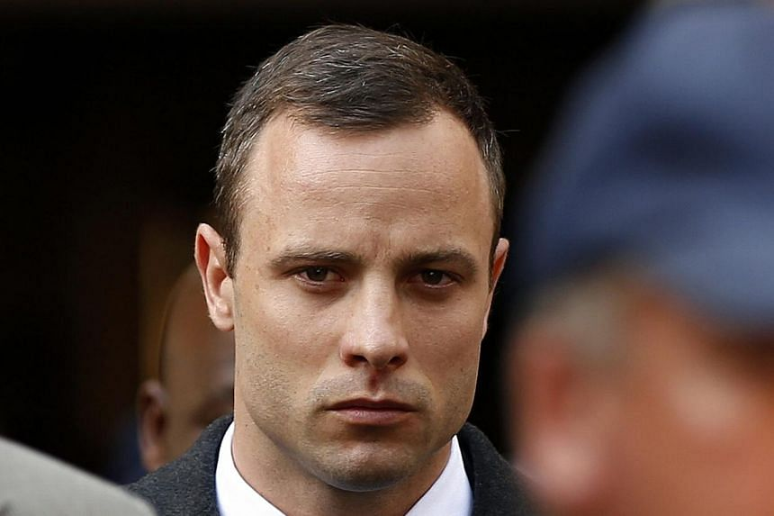 Oscar Pistorius leaves after attending his trial at the high court in Pretoria on April 7, 2014. The prosecution angrily accused Oscar Pistorius of tailoring evidence and overplaying his deep fear of crime on Friday, April 11, 2014, to justify s