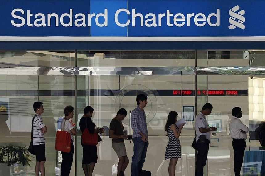 """People queue up outside a Standard Chartered Bank branch before operation hours at the central business district in Singapore on Jan 23, 2014.The Monetary Authority of Singapore says it has taken """"appropriate supervisory actions"""" against Standa"""