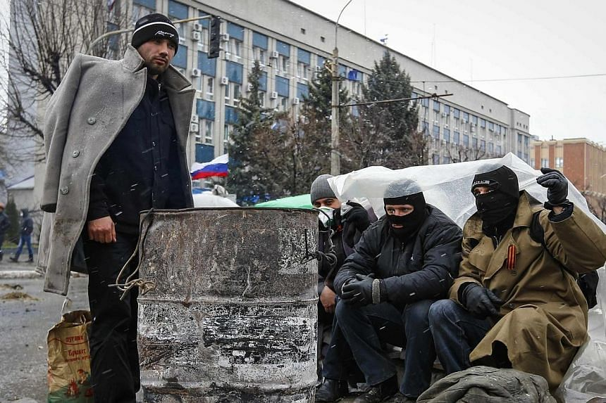 Pro-Russian protesters warm themselves in front of the seized office of the SBU state security service in Luhansk, in eastern Ukraine on April 11, 2014. US President Barack Obama threatened fresh sanctions against Moscow if it escalates the cris