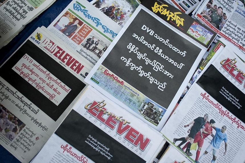 """Newspapers with a black front page (left) are displayed at a stall in Yangon on April 11, 2014, after Zaw Pe, a journalist for the Democratic Voice of Burma (DVB) news website, was convicted of trespassing and """"disturbing a civil servant"""" by a court"""