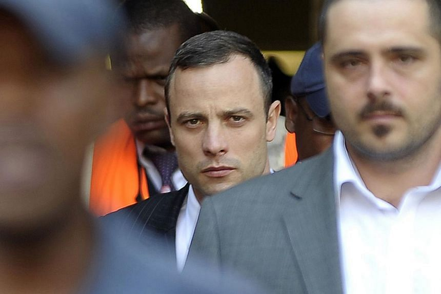 South African Paralympic track star Oscar Pistorius (centre) leaves the North Gauteng Hight Court in Pretoria on April 11, 2014, during his ongoing murder trial. Oscar Pistorius' three-day cross-examination reached a dramatic climax on Friday wh