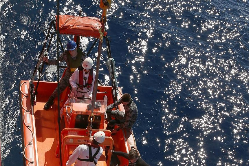 Crew members in a fast response craft from the Australian vessel Ocean Shield being lowered onto the water to search for debris from Malaysia Airlines Flight MH370 in the southern Indian Ocean on Monday. -- PHOTO: AGENCE FRANCE-PRESSE