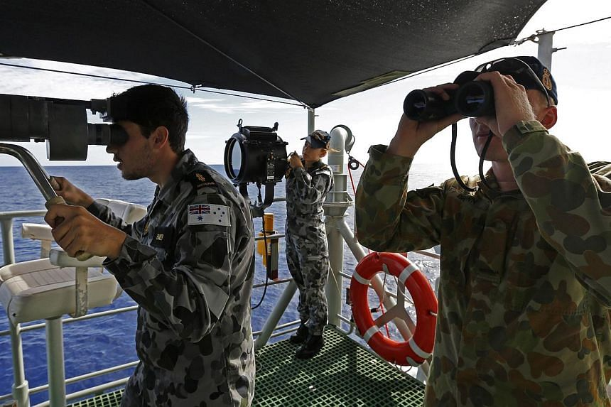 Communications and Information Systems (CIS) Able Seaman Andrew Bailey (left), Communications and Information Systems, Seaman Georgina Brooks (centre) and Gunner (GNR) Richard Brown watching HMAS Success as HMAS Perth approaches for a replenishment a