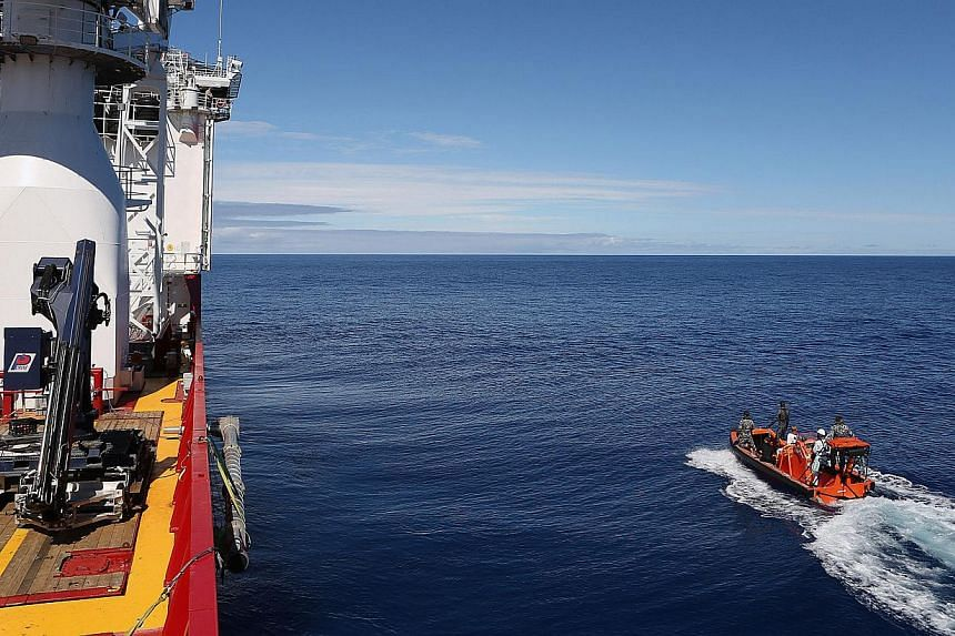 Crew members are seen aboard a fast response craft (right) from the Australian Defence Vessel Ocean Shield (left) as they continue to search for debris of the missing Malaysian Airlines flight MH370 in the southern Indian Ocean on April 8, 2014. -- F