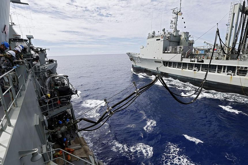 Crew aboard the Australian Navy ship HMAS Perth watch lines as they are refuelled by HMAS Success during a replenishment at sea, as they continue to search for missing Malaysian Airlines flight MH370 on April 10, 2014. -- PHOTO: REUTERS/AUSTRALIAN DE