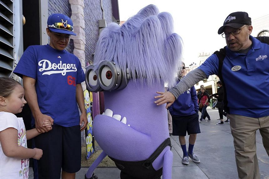 A purple Minion character meets park visitors at the new Despicable Me Minion Mayhem ride during technical rehearsals for the new attraction at Universal Studios Hollywood in Universal City, California on March 28, 2014. -- FILE PHOTO: REUTERS