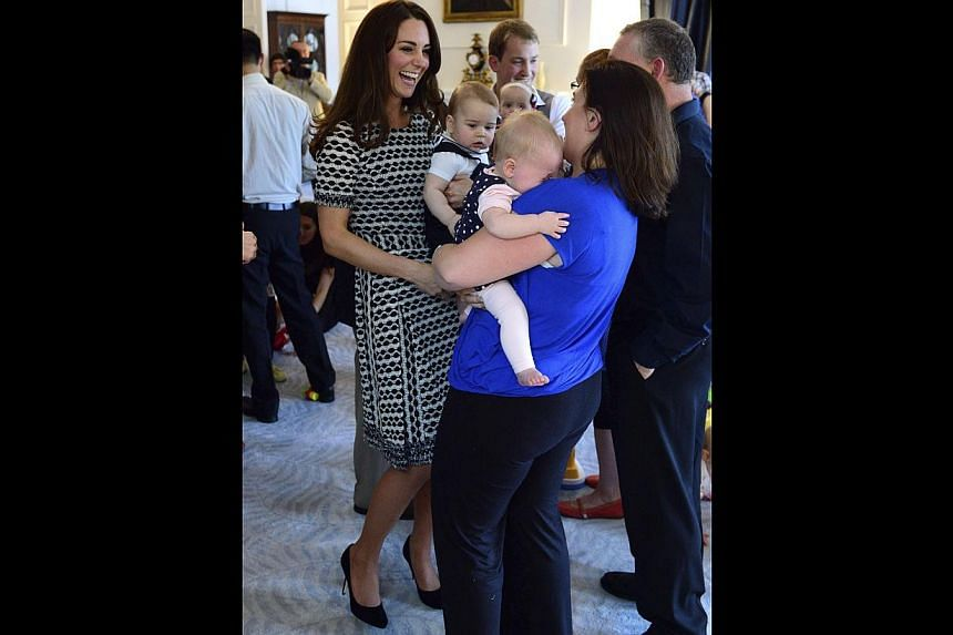 The Duchess of Cambridge holds her son Prince George as she talks to other parents at a Plunket play group event at Government House in Wellington. -- PHOTO: REUTERS