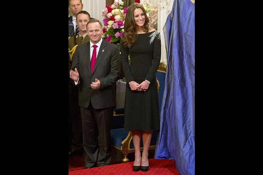 Catherine, the Duchess of Cambridge, with New Zealand Prime Minister John Key during the unveiling of a portrait of Queen Elizabeth II by New Zealand artist Nick Cuthell during a state reception at Government House in Wellington on April 10, 2014. --