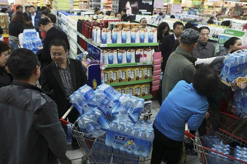 People line up to buy cartons of bottled water at a supermarket after reports on heavy levels of benzene in local tap water, in Lanzhou, Gansu province on April 11, 2014. -- PHOTO: REUTERS