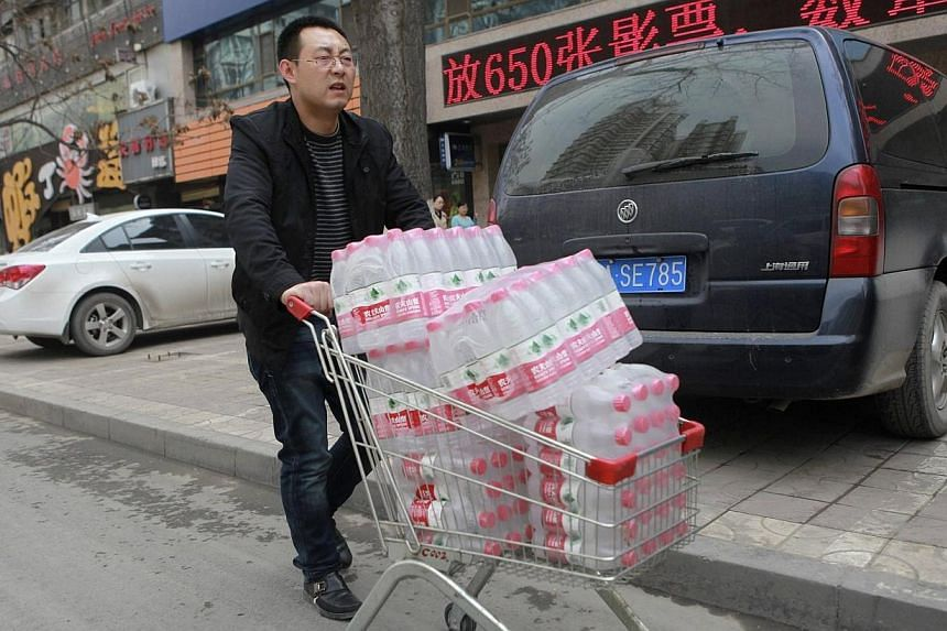 A man pushes a shopping cart filled with bottled waters after reports on heavy levels of benzene in local tap water, in Lanzhou, Gansu province April 11, 2014. -- PHOTO: REUTERS