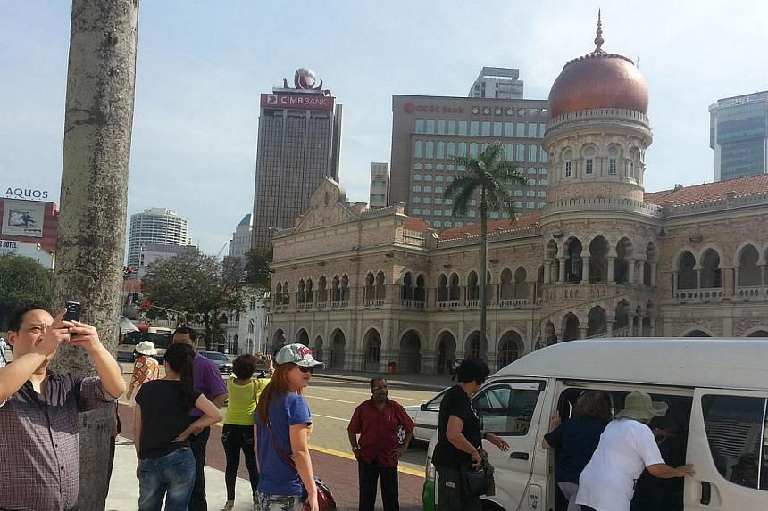 Tourists from China taking in the view from Kuala Lumpur's Dataran Merdeka.Chinese tourists will return to Malaysia once the MH370 crisis and the kidnapping of one of its nationals in Sabah have been resolved, said Malaysia's Tourism and Cult