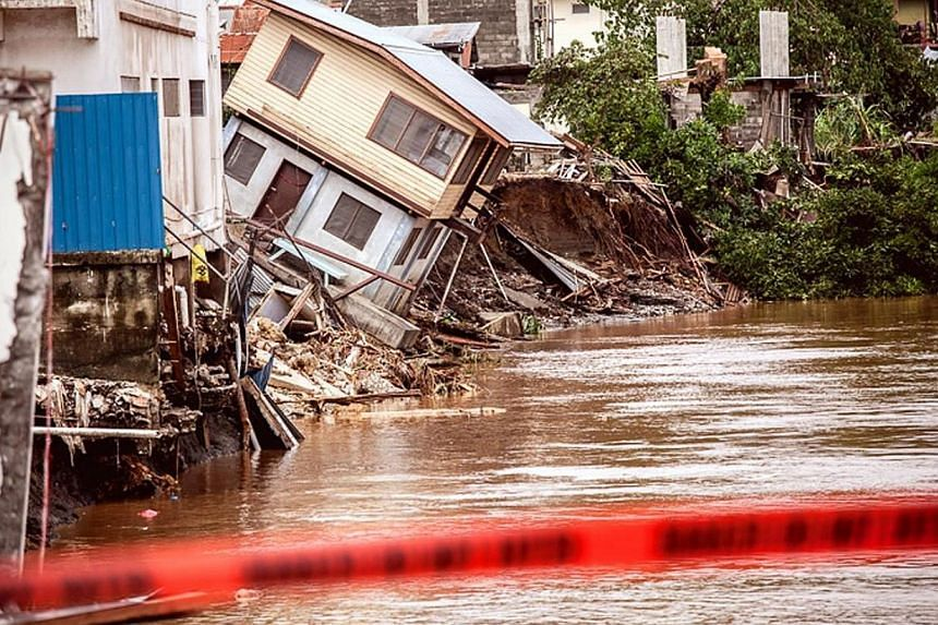 Houses can be seen falling into the Mataniko River as a result of severe flooding near the capital Honiara in the Solomon Islands in this picture released by World Vision on April 6, 2014. -- FILE PHOTO: REUTERS
