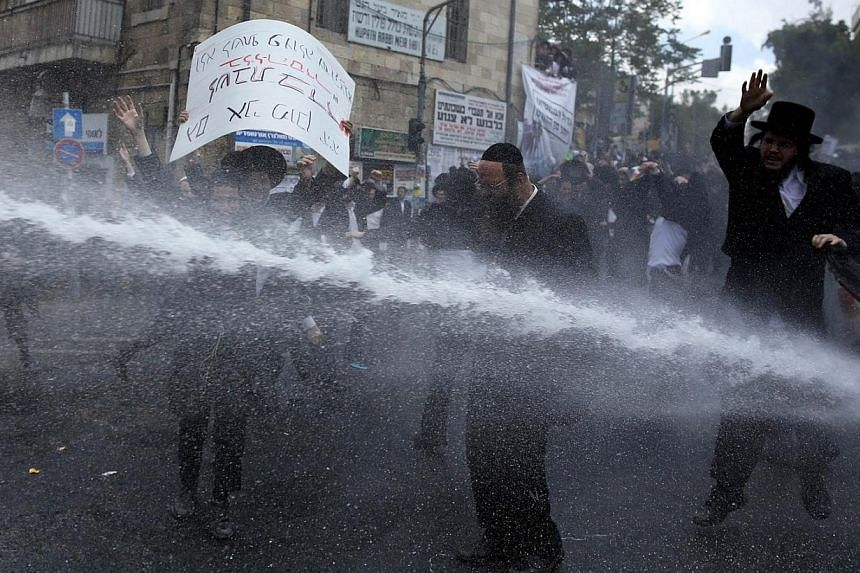 Israeli police (unseen) use a water cannon to disperse Ultra-Orthodox Jews taking part in a demonstration against compulsory military service in Jerusalem on April 10, 2014. -- PHOTO: AFP