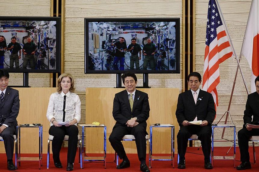 United States Ambassador to Japan Caroline Kennedy (2nd left) and Japan's Prime Minister Shinzo Abe (centre) communicate with Japanese astronaut and International Space Station (ISS) commander Koichi Wakata (center of the screen) at Abe's official re