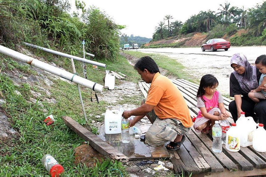 A family collecting spring water in Puncak Alam. With no end in sight for the lengthy water crisis, some Malaysians are getting savvy at meeting their bathing and washing needs. -- PHOTO: THE STAR PUBLICATION
