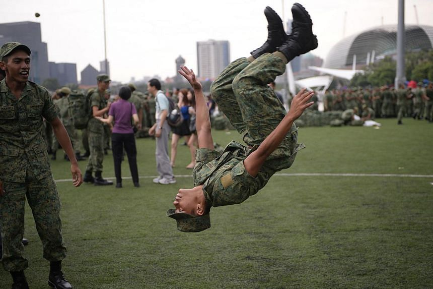 Close to 20,000 spectators gathered at the Marina Bay Floating Platform to cheer their friends and family taking part in the Singapore Armed Forces' (SAF) first integrated military parade on Saturday morning.-- ST PHOTO: MARK CHEONG