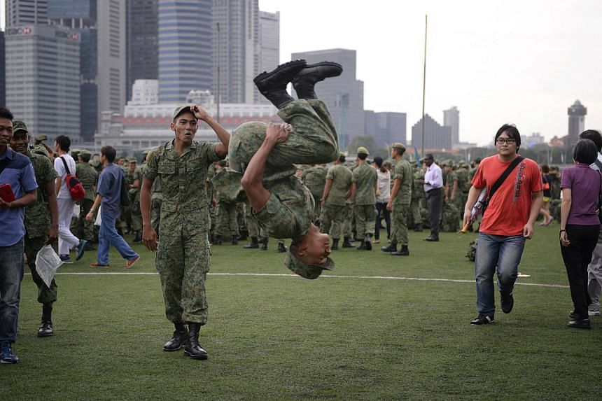 Close to 20,000 spectators gathered at the Marina Bay Floating Platform to cheer their friends and family taking part in the Singapore Armed Forces' (SAF) first integrated military parade on Saturday morning. -- ST PHOTO: MARK CHEONG