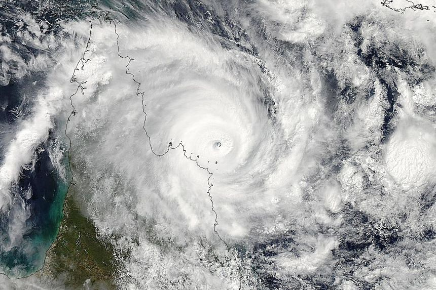 This Nasa Earth Observatory handout satellite image received on April 12, 2014 acquired by Aqua's Moderate Resolution Imaging Spectroradiometer (MODIS) on April 11 shows Tropical Cyclone Ita as it bore down on Australia's Cook Peninsula. -- PHOTO