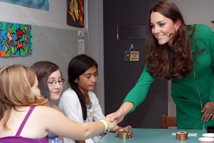 Britain's Duchess of Cambridge Catherine (right) greets children during a visit to Waikato Hospice Rainbow Place in Waikato on April 12, 2014. -- PHOTO: AFP
