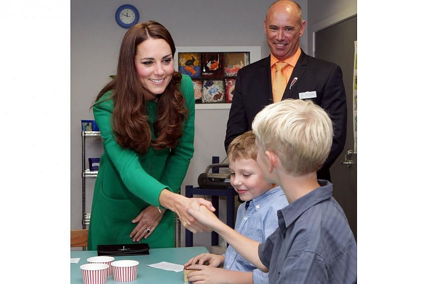Britain's Duchess of Cambridge Catherine (left) greets children alongside Craig Tamblyn during a visit to Waikato Hospice Rainbow Place in Waikato on April 12, 2014. -- PHOTO: AFP