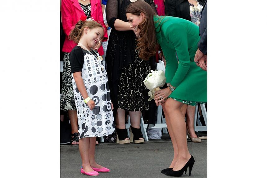 Britain's Duchess of Cambridge Catherine (right) speaks with Kaiya Miller after receiving flowers during a visit to Waikato Hospice Rainbow Place in Waikato on April 12, 2014. -- PHOTO: AFP