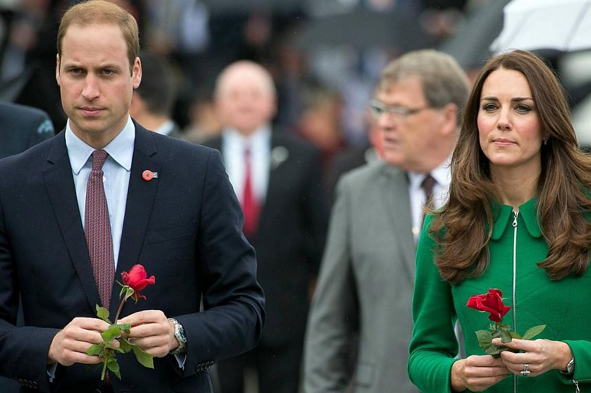 Britain's Prince William and his wife Catherine, Duchess of Cambridge, hold flowers as they prepare to lay them on the war memorial in Cambridge on April 12, 2014. -- PHOTO: REUTERS
