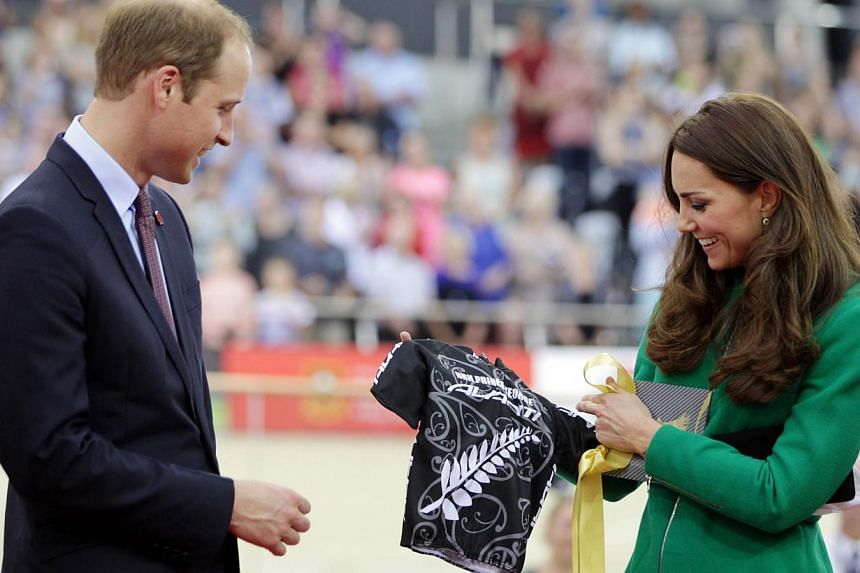 Britain's Prince William and his wife Catherine, Duchess of Cambridge, are presented with a cycling shirt for their son Prince George at the opening of the National Cycling Centre of Excellence and Velodrome, in Cambridge on April 12, 2014. -- PHOTO:
