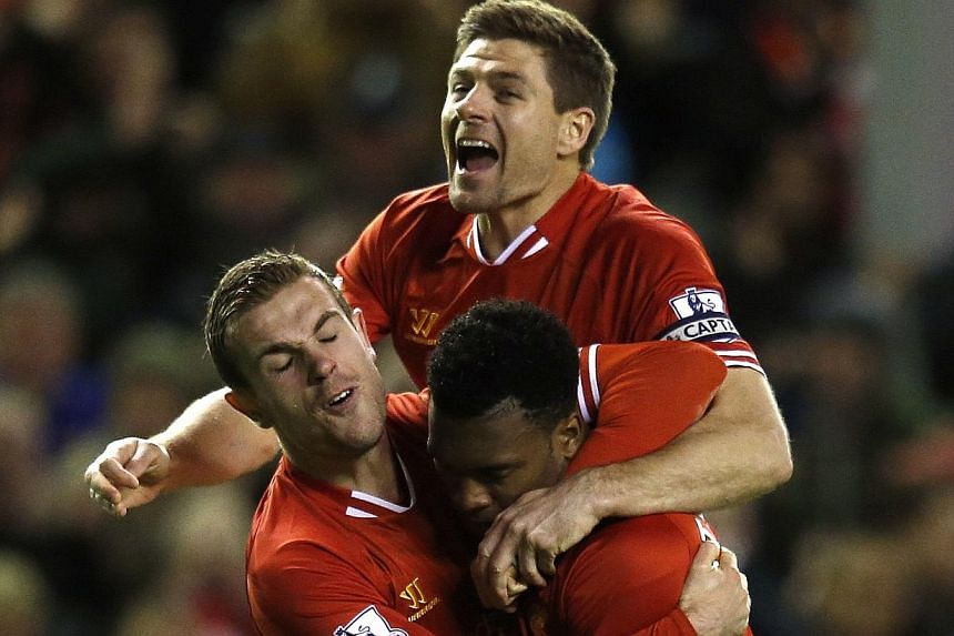 Liverpool's Daniel Sturridge (right) celebrates with teammates Steven Gerrard (centre) and Jordan Henderson after scoring a goal during their English Premier League soccer match against Sunderland at Anfield in Liverpool, northern England on March 26
