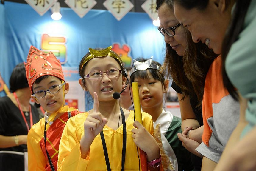 Dressed in costumes from the Chinese literary classic Journey To The West, Primary 4 pupils from Mee Toh School (from left) Kiefer Ong, Chen Bailin and Annabelle Yeow speaking to visitors at the ExCEL Fest yesterday. Pupils in the school study the bo