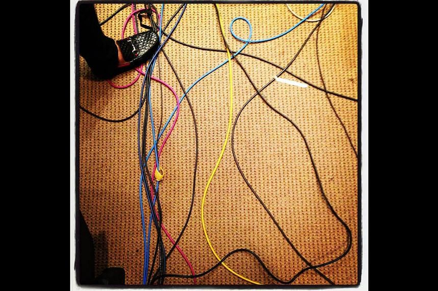 The wires of the electronic media criss-cross the floor of a Kuala Lumpur hotel during a press conference on missing Flight MH370. -- ST PHOTO: NEO XIAOBIN