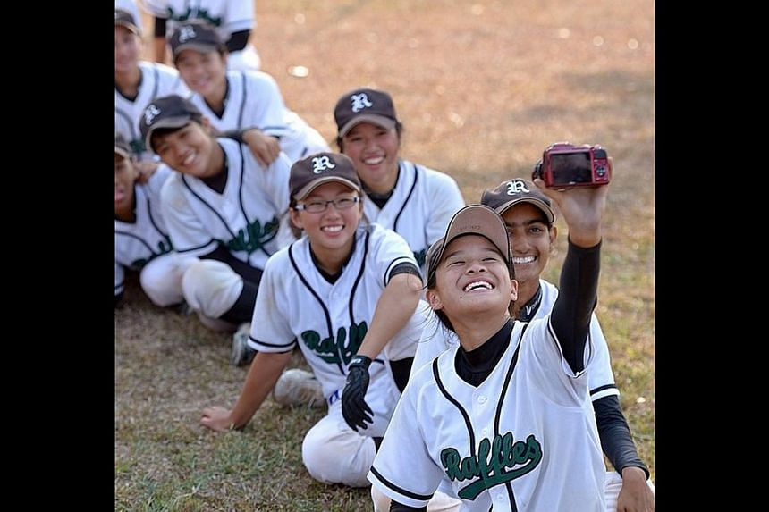 Raffles Girls' Secondary School student Cacia Tan taking a selfie with her softball teammates. -- ST PHOTO: DESMOND WEE